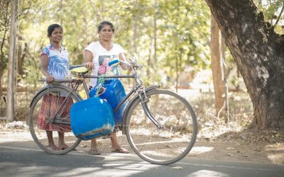 village women carrying water bottles
